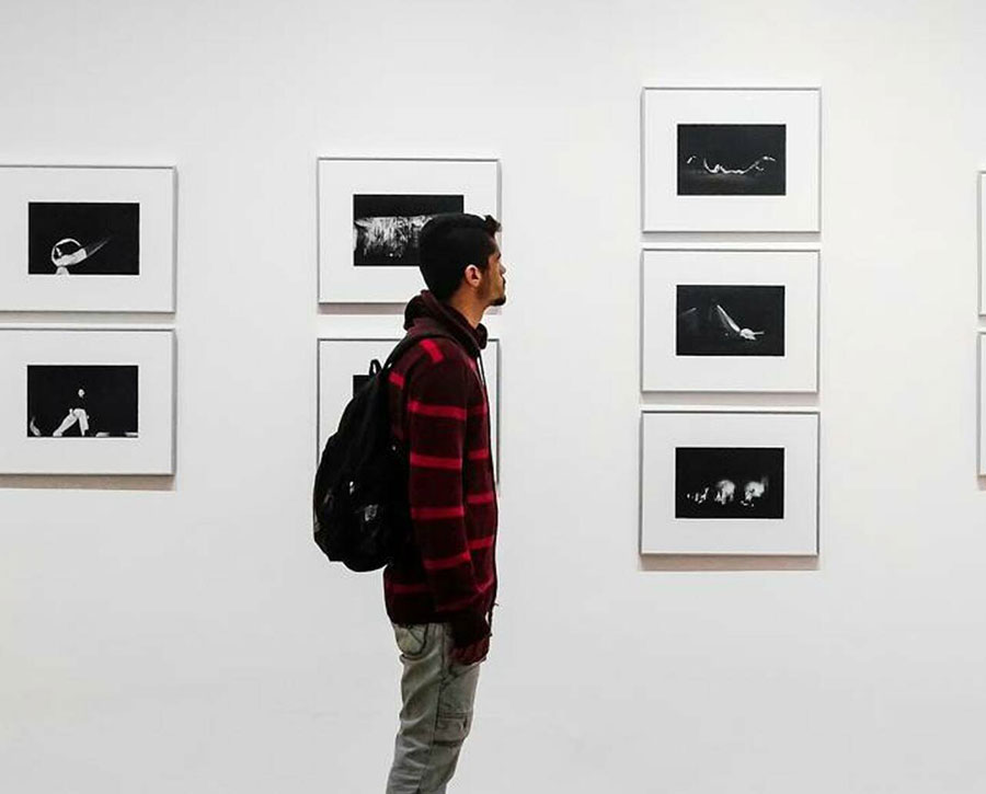 Person with backpack in art gallery observing framed photographs on wall.