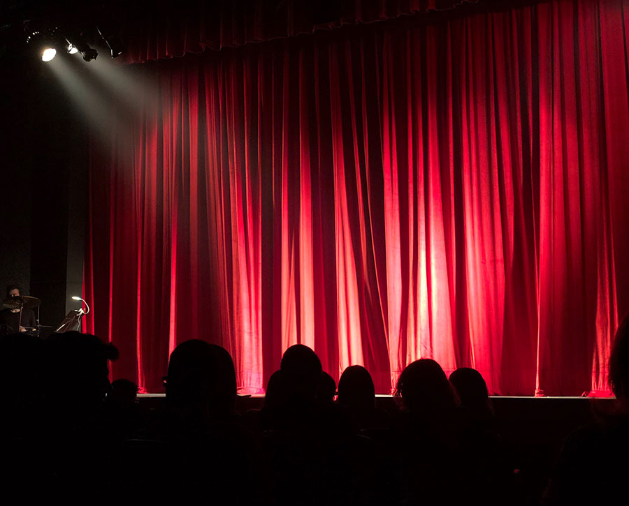 Comedy club stage with bright stage lighting, closed curtains, and audience patrons.